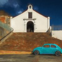 blue VW bug in front of stairs leading to a small white church
