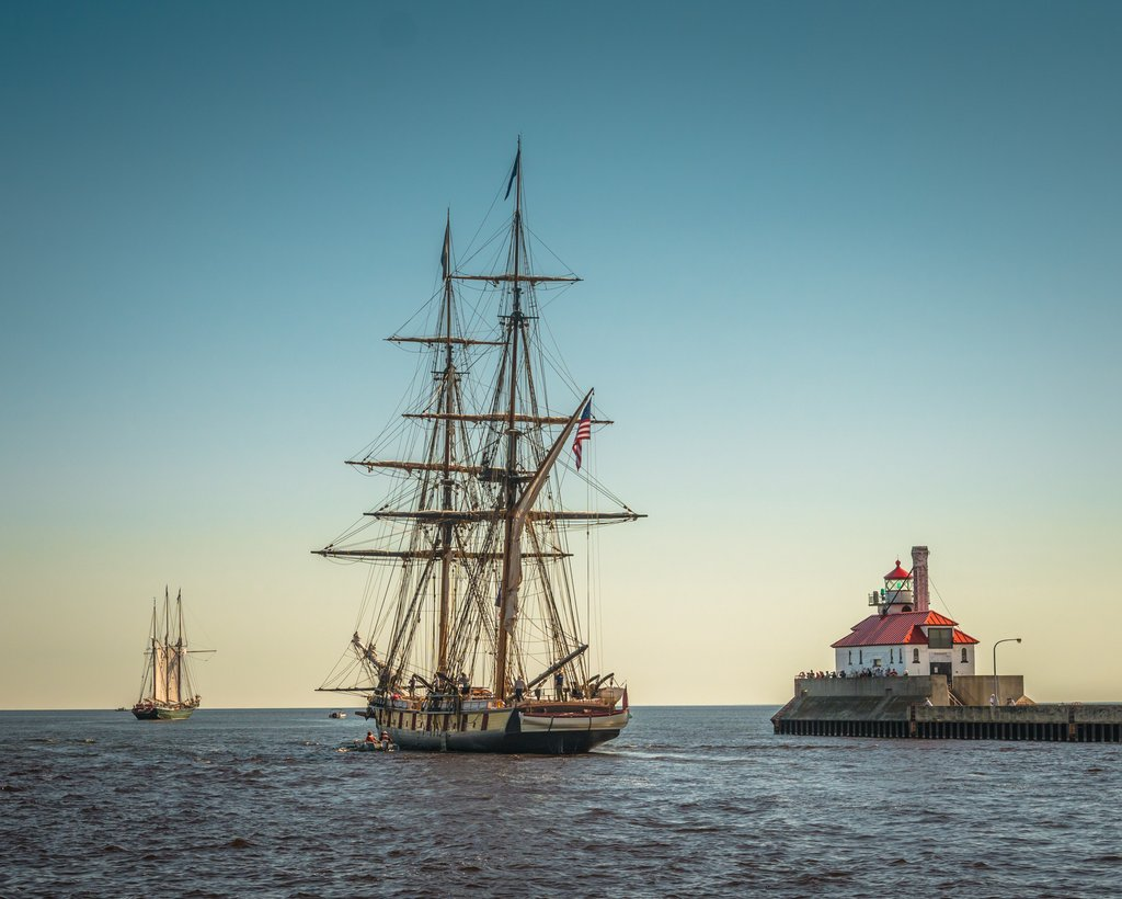 two tall ships and harbor light